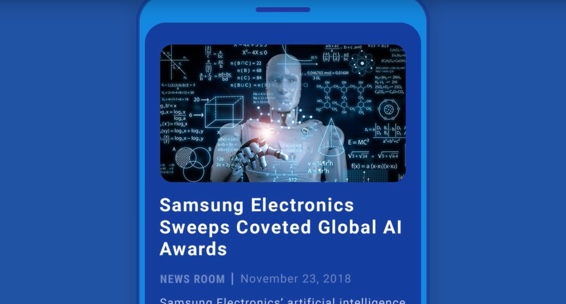 "A robot stands in front of a screen. ""Samsung Electronics Sweeps Coveted Global AI Awards"" is laid out underneath it."