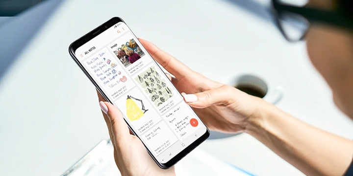A woman's hands using a smartphone to access Samsung Notes.
