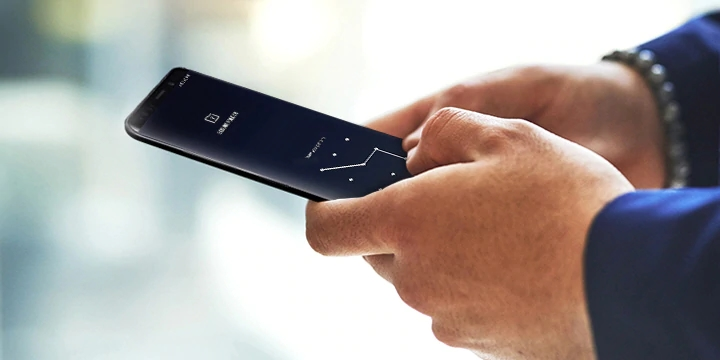 A man's hands holding a smartphone showing a pattern unlock screen ready to access Secure Folder.