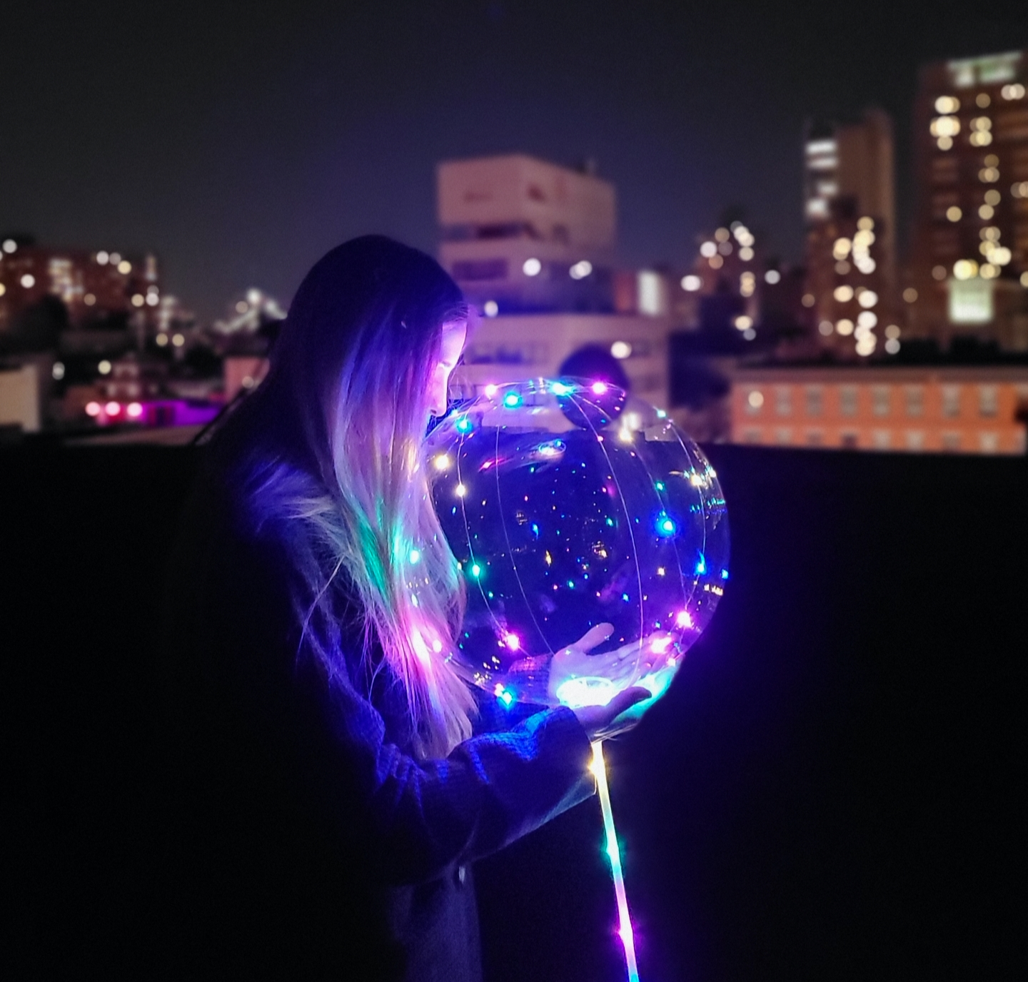 Summer night photography of a woman holding a glowing LED balloon while bokeh lights glow in the background