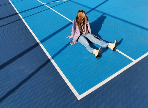 Golden hour photography shot of woman sitting on the tennis court