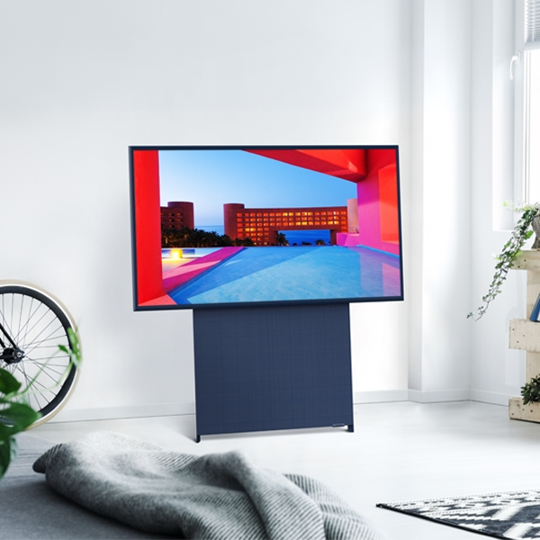 The Sero stands in a white room, with the screen in horizontal mode, displaying a building on the screen.