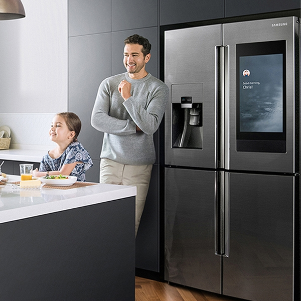 The man is standing in front of the refrigerator and the child is sitting at the table eating and laughing.