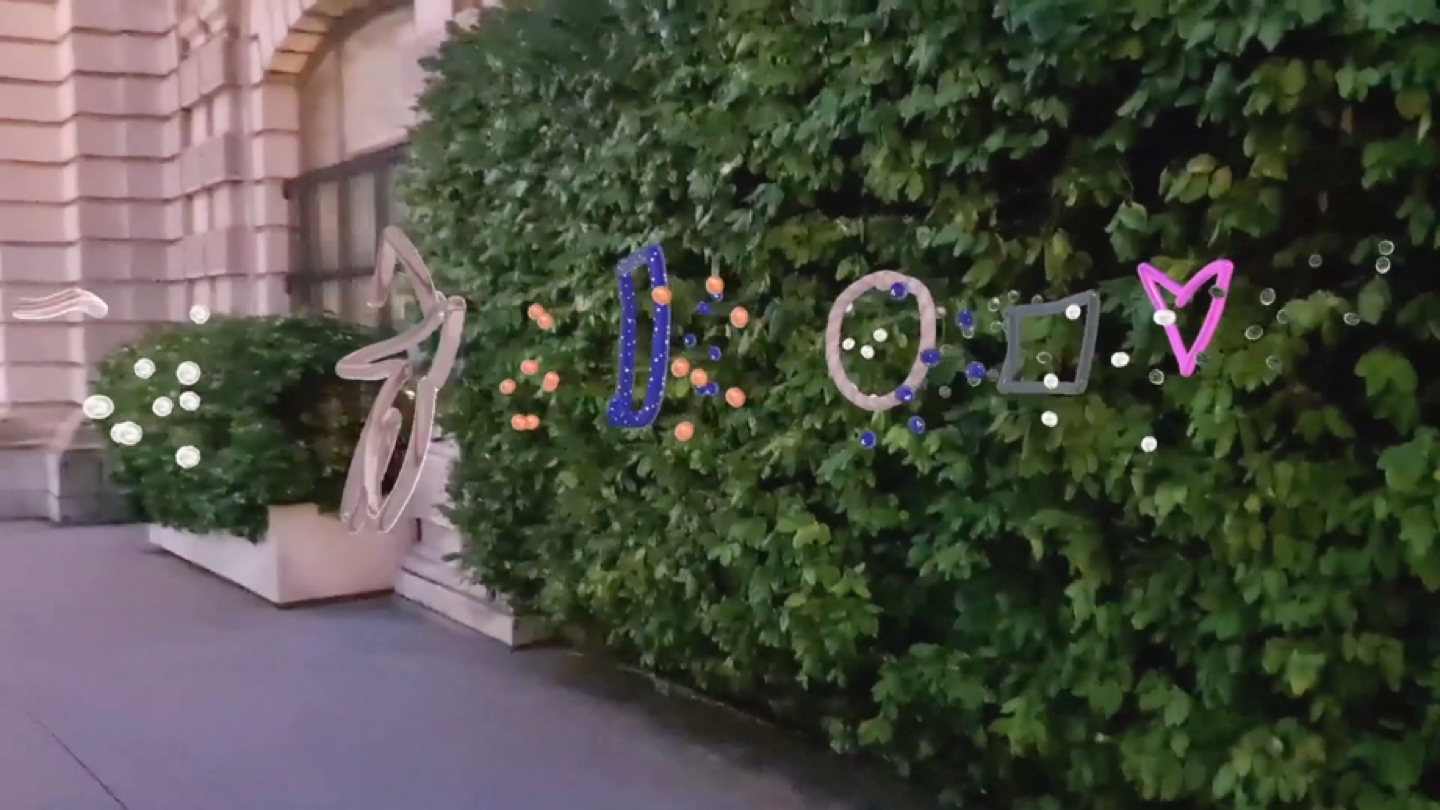A video still of polka dots, a star, circle, square and heart AR doodles against a backdrop of greenery