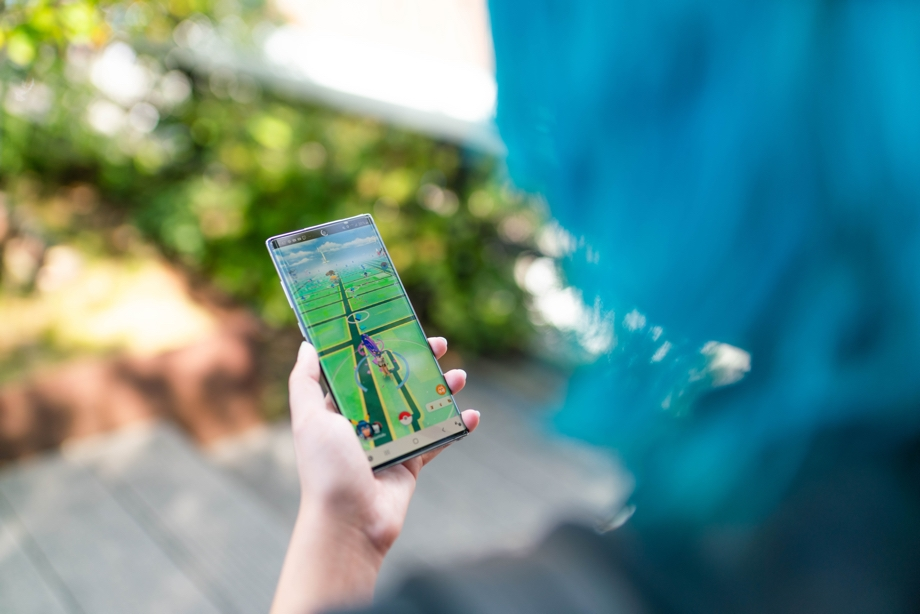 A lady standing outside and holding a phone with Pokemon GO visible on the screen. The image is shot from over her shoulder.