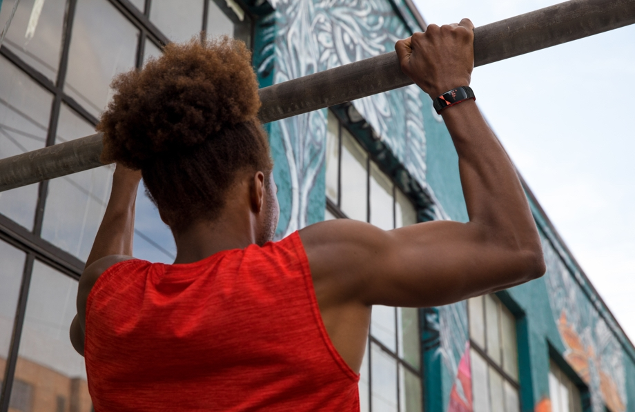 A man does pull ups while a Samsung wearable tracks his progress.