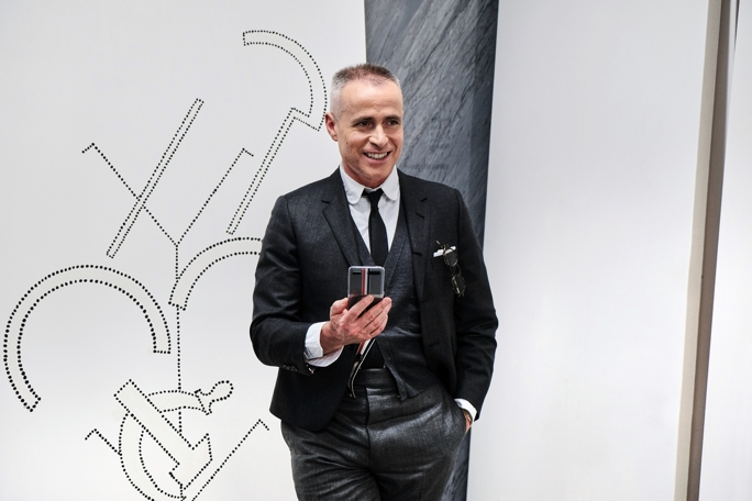 Thom Browne holds an unfolded Galaxy Z Flip Thom Browne Edition phone in his palm and smiles as he looks ahead and slightly toward the right