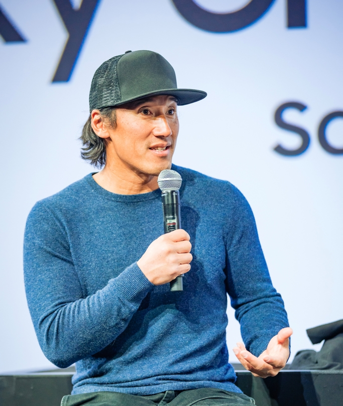 JimmyChin wearing a baseball cap and a blue sweater and speaking on stage at the Creator Lounge Creators Talk