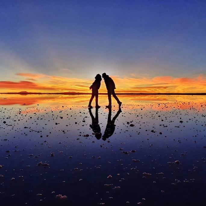 An image of a couple standing on a reflected surface with a  colorful sunset in the background, they are in playful poses facing eachother