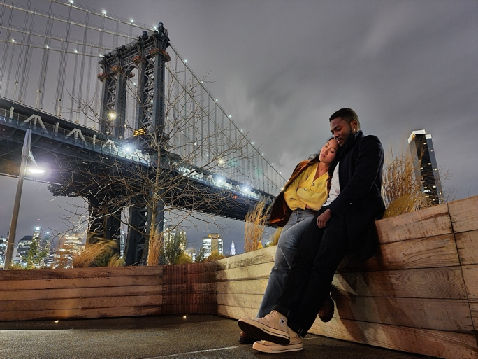 A couple sitting on a wooden surface with the Manhattan Bridge in the background, the scene is shot from a low angle