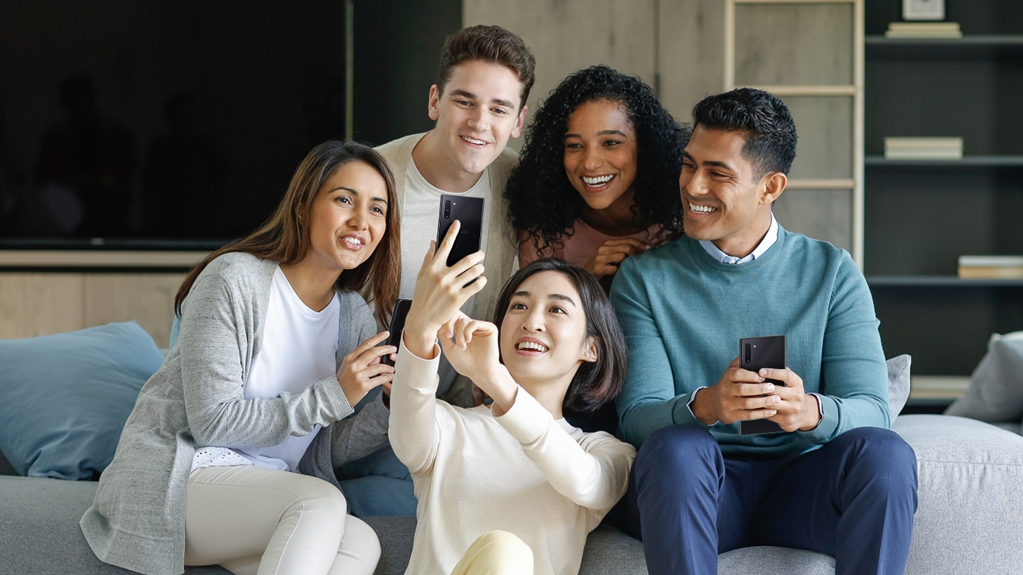 Five mixed adults of a multi-racial race are enjoying watching their cell phones.