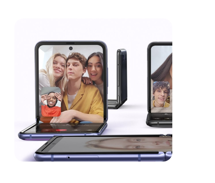 The Galaxy Z Flip is positioned in four diffeent angles. One is facing the viewer and shows a video conference going on. Three people are in the screen while another is in the lower eft hand corner. Another phone is laying flat, one is the background while another is cut off on the right.