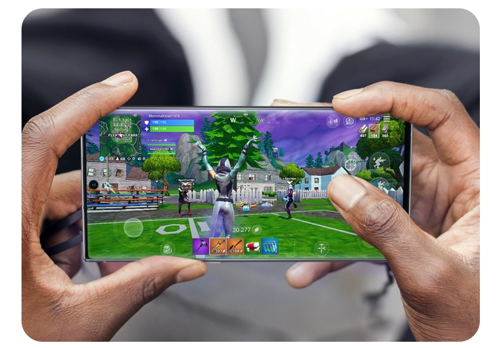 Close up pair of hands holding a Galaxy 5G phone in landscape orientation playing Fortnite.