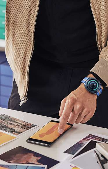Image of person looking at photos on Galaxy Note8 wearing Gear Sport with Premium Nato strap in blue and orange
