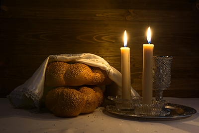Challah bread and candles on a table