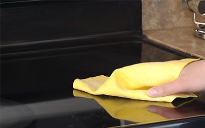 Wiping the cooktop surface with a yellow cloth