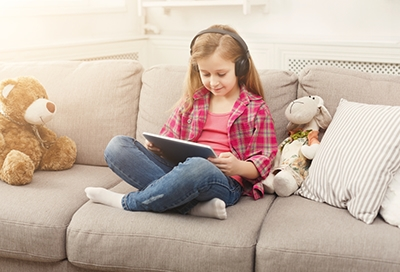 Little girl using a Bluetooth headset with tablet