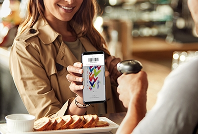 Woman holding up phone with Samsung Pay