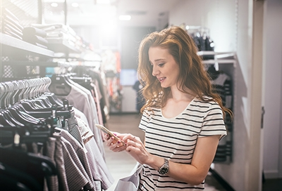 Girl using her phone in a clothing store