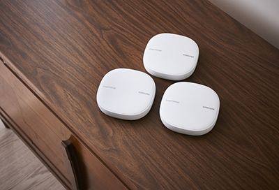 Three Samsung Wifi hubs on a table