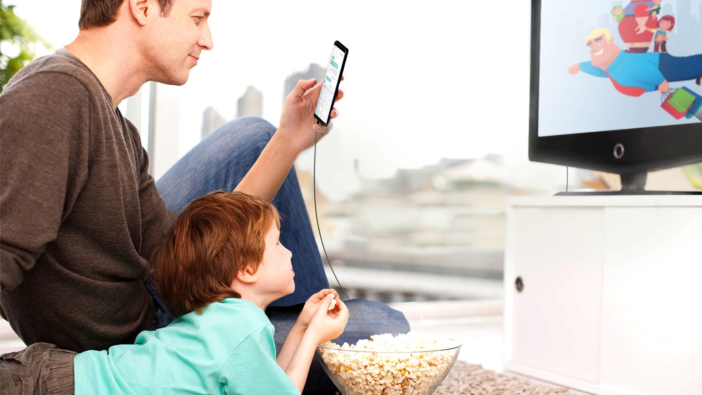 A father and son sitting on the floor in front of the TV. The son is watching a YouTube video and eating popcorn as the father texts on his smartphone while it is connected to the TV.