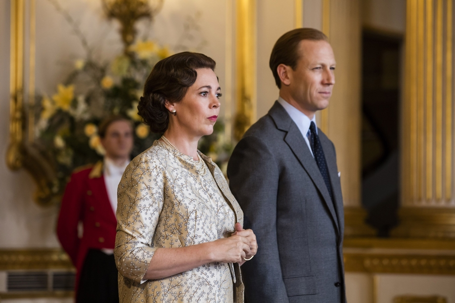 Scene from hit series The Crown via Netflix mobile app that shows characters Queen Elizabeth the 2nd and Prince Phillip standing together with steely expression on their faces