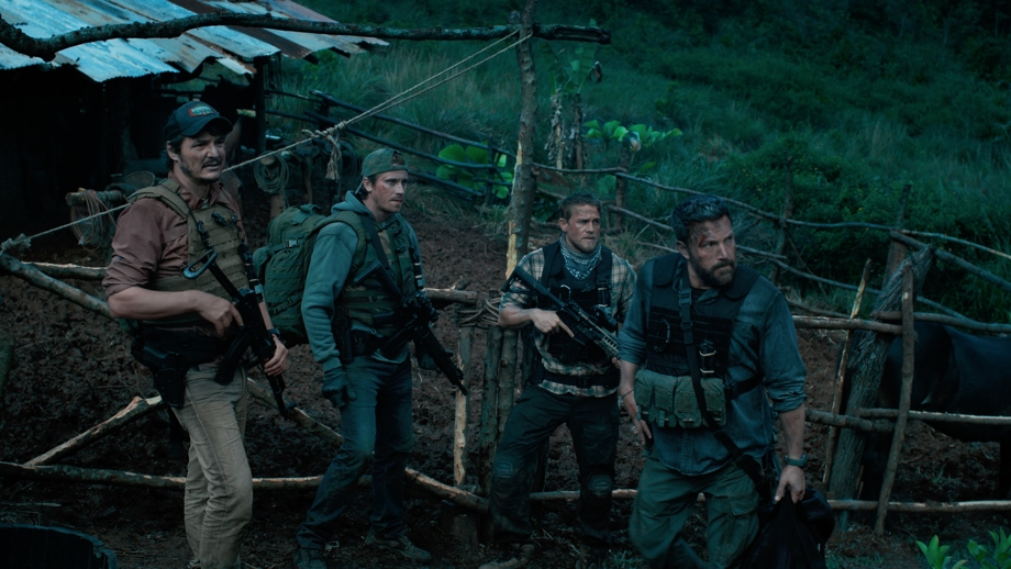 Scene from Netflix Originals movie Triple Frontier via Netflix mobile app that shows four, armed ex-US Special Forces soldiers wearing bullet-proof vests while standing in what looks like a field