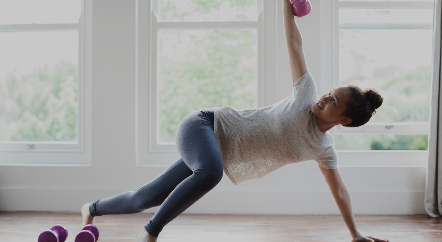 Woman practicing yoga workout at home using kettlebells