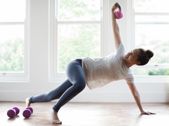 Woman practicing yoga with kettlebells