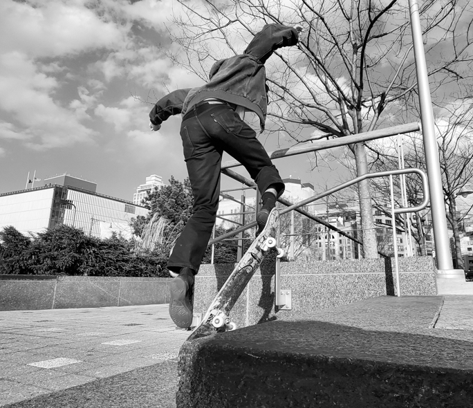 Man practicing tricks on skateboard using a stair railing