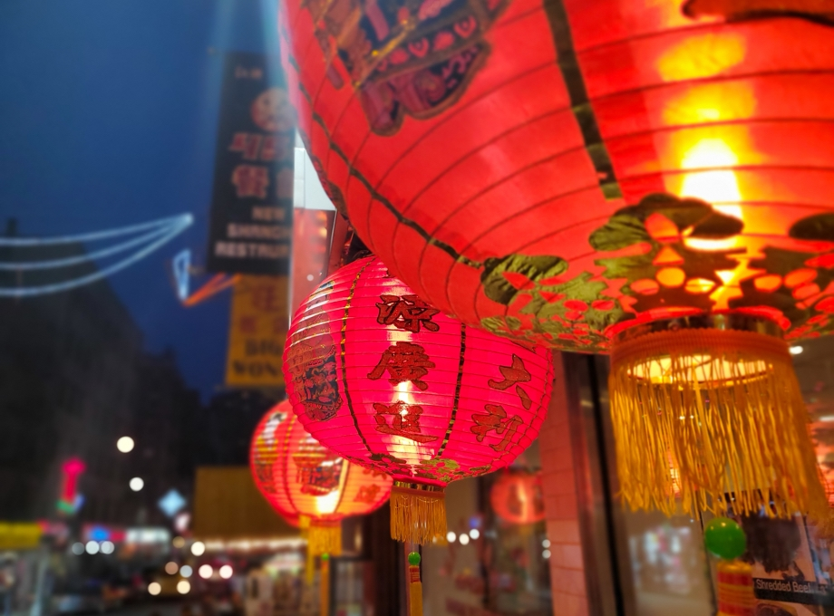 Close-up shot of three chinese lanterns with bokeh lights in the background