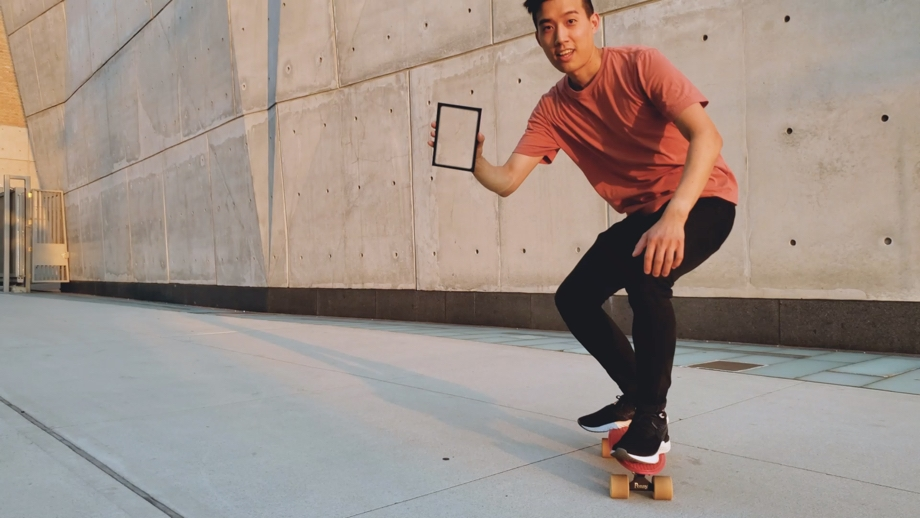 A video still of a guy on a skateboard holding a black frame in front of a concrete wall