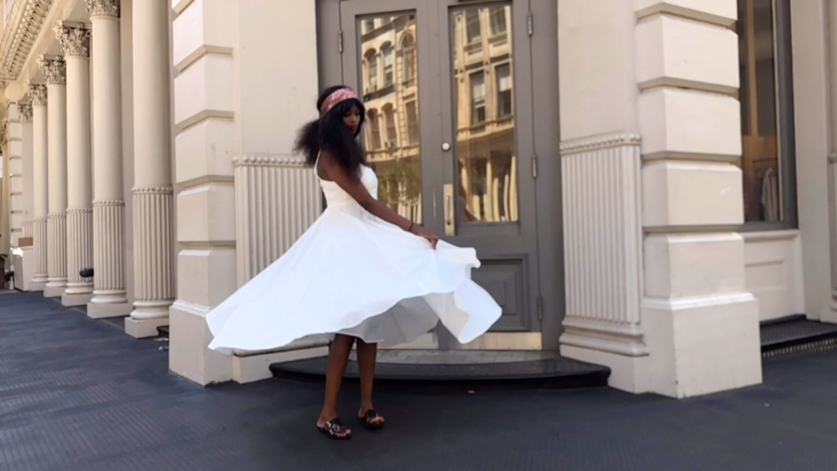 A video still of a lady standing in front of a doorway holding onto a billowing white dress