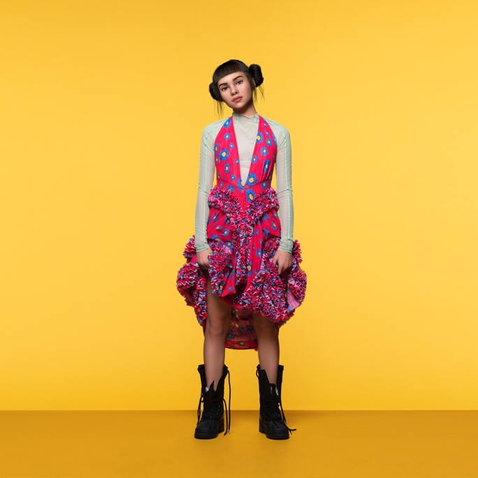 A full-body, promotional shot of Lil Miquela wearing a brightly colored dress while looking confidently into the camera