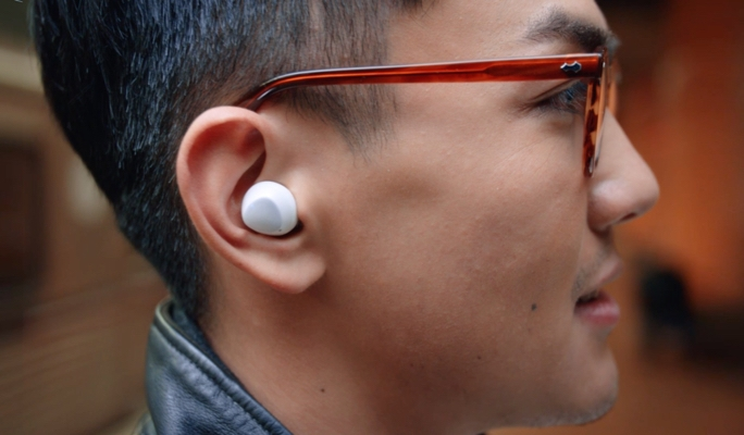 A profile shot of a man wearing a white Galaxy Buds+ earbud in his right ear