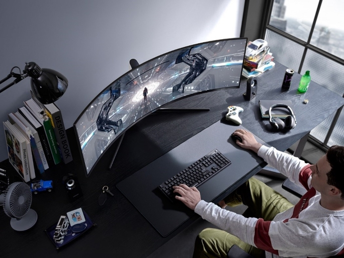 Overhead shot of a man at a desk gaming on a curved monitor