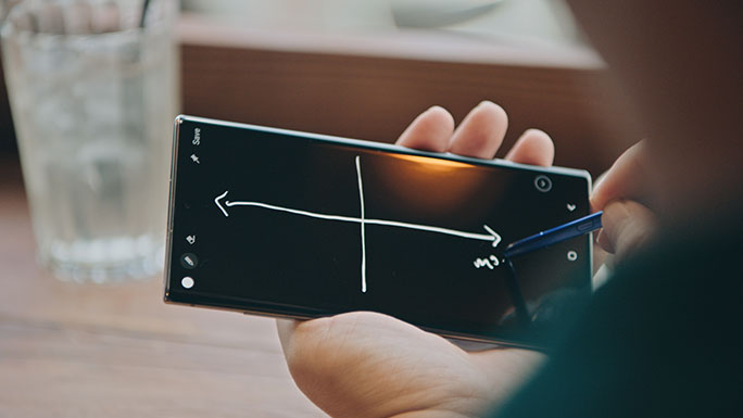 A close-up shot of a Galaxy Note10 and S Pen in Kevin Lin's hands. He is using the S Pen to draw lines and make notes on the phone's black screen.