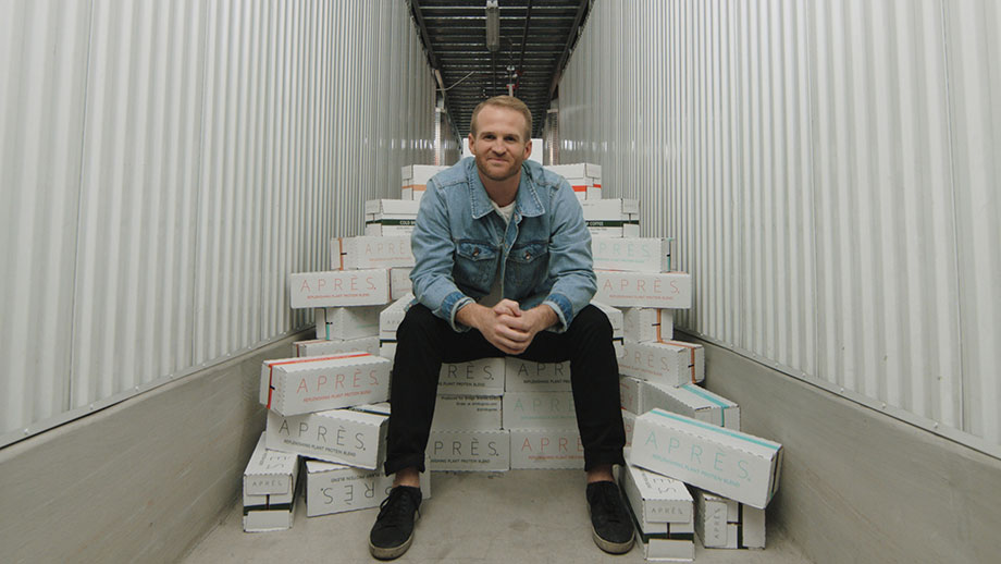 A screen grab of a video  showing entrepreneur Sonny McCracken sitting on a pile of Aprè protein drink boxes.