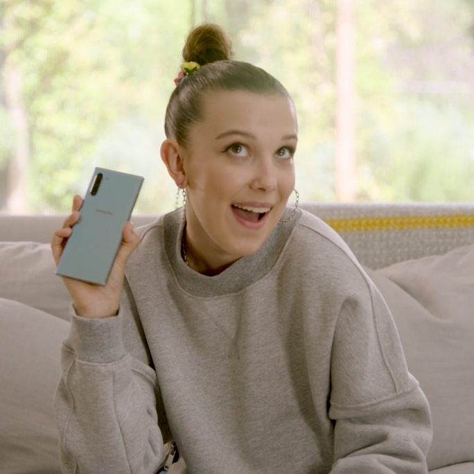 Video still of Millie Bobby Brown sitting on a couch, holding up an Aura Glow Galaxy Note10