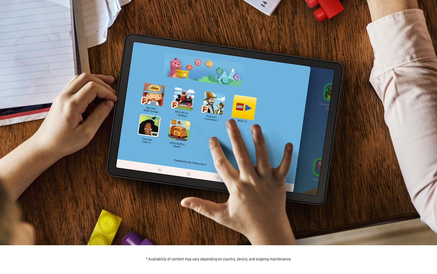 Simulated image of a tablet on a table surrounded by papers and LEGO blocks. A child's hands are nearby and their right hand is touching the tablet screen. Onscreen is the LEGO App UI, showing different kinds of entertainment your child can experience.