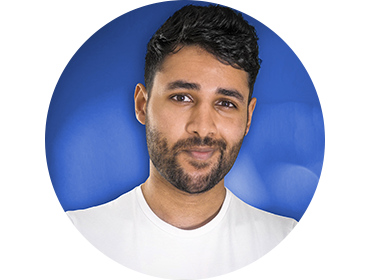 Headshot of Arun Maini against a blue background. He's wearing a T-shirt and smirking at the camera