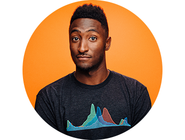 Headshot of Marques Brownlee against an orange background. He's wearing a T-shirt and ginning slightly with his eyebrows raised