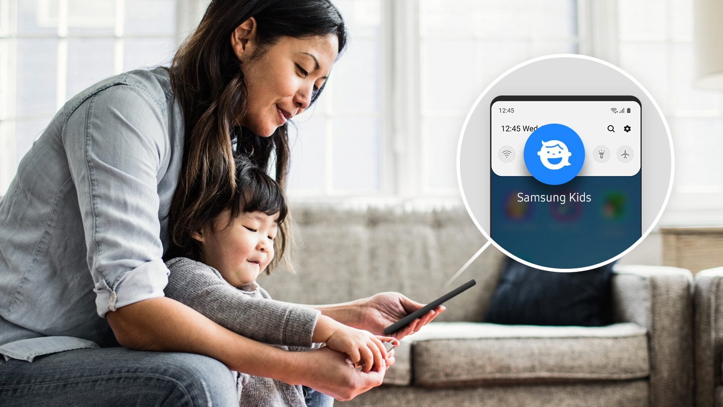 Simulated image of a woman with her child in their living room. The woman is holding a smartphone, and there is a simulated overlay of her screen with the Kids Home icon enlarged, showing how you can access Kids Home easily on the Quick panel.
