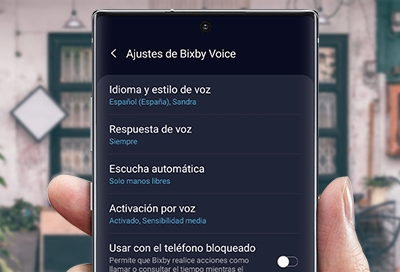 Hand holding phone with the settings and language option displaying on screen