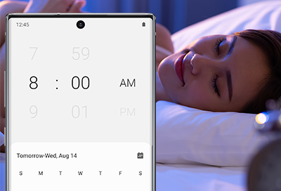 Woman sleeping with Note10 showing Alarm screen