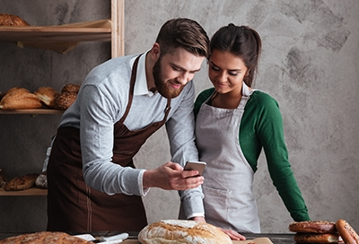 Man and woman looking at phone while baking bread
