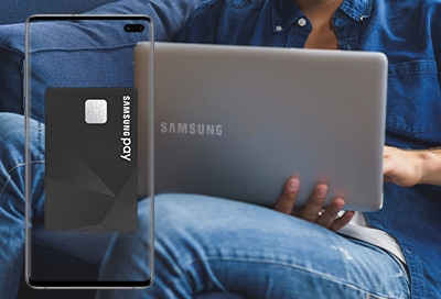 Man on laptop with Samsung Pay opened on his phone