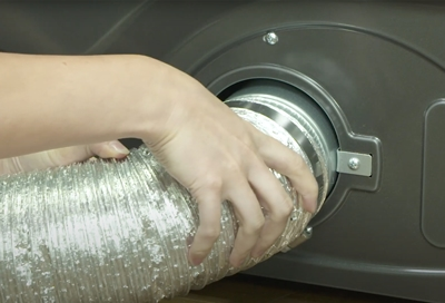 A person checking  the Samsung dryer duct