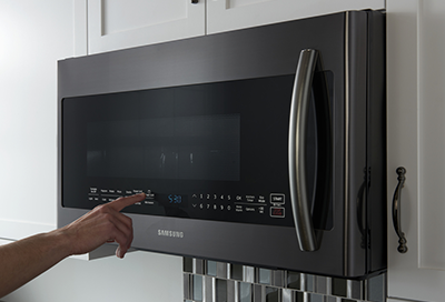 Hand pressing buttons on a Samsung over the range microwave