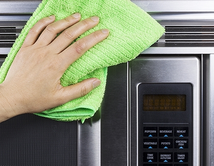 Person using microfiber cloth to clean the microwave's exterior